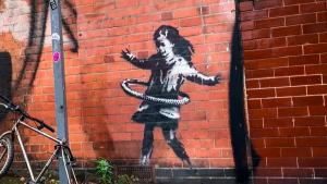 New Banksy Street Mural Shows Girl Using Bike Tire as Hula Hoop